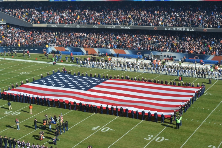 Service members from all five military branches unfurl the national ensign during ceremonies prior to Sunday's football game between the Chicago Bears and Detroit Lions at Soldier Field in Chicago, Nov. 10, 2013. Pregame and halftime ceremonies helped pay tribute to veterans in commemoration of Veterans Day. (U.S. Coast Guard photo by Chief Petty Officer Alan Haraf)